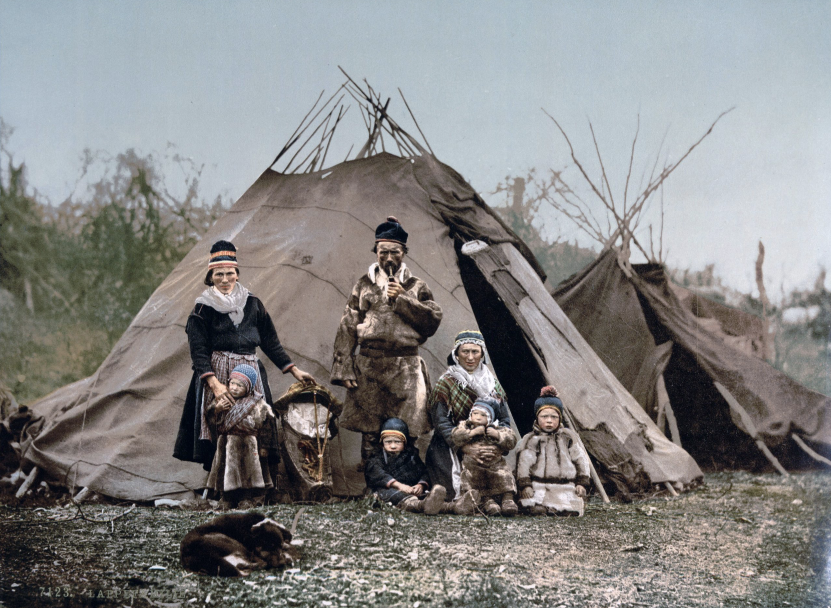A Sami family in front of a goahti in the foreground and a lavvu in the background (the picture is taken around 1900). (Public domain: United States Library of Congress's Prints and Photographs division).